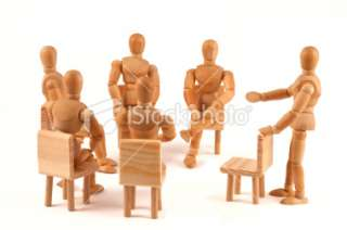 group of people talking about   wooden mannequins in circle Royalty